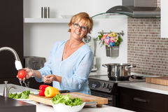 Mature woman cooking in new kitchen Royalty Free Stock Photo