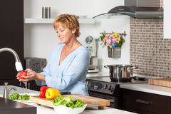 Mature woman cooking in new kitchen Royalty Free Stock Photos