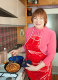 Mature woman cooking pancakes Royalty Free Stock Photos