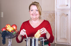 Mature woman cooking pasta. Stock Image