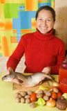 Mature woman is cooking red  fish Stock Image
