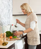 Mature woman cooking  tasty soup Royalty Free Stock Images