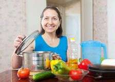 Mature woman cooking with vegetables Stock Photography