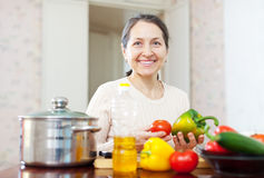 Mature woman cooking veggie lunch Royalty Free Stock Photography