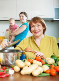 Mature woman cooking veggie lunch in kitchen Royalty Free Stock Image