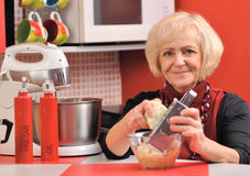 Mature woman cooks meal in red kitchen. Stock Images