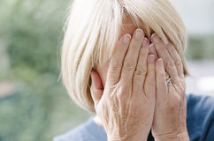 Mature woman covering her face with her hands. Royalty Free Stock Photography