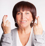 Mature woman with crossed fingers Stock Images