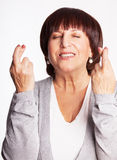 Mature woman with crossed fingers Royalty Free Stock Photos