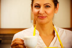 Mature woman with cup of coffee in kitchen. Royalty Free Stock Photo