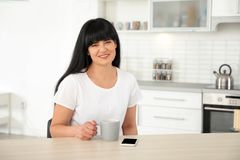 Mature woman with cup of coffee sitting at table royalty free stock photo