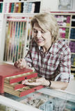 Mature woman customer in sewing store Stock Photo