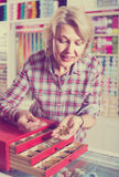 Mature woman customer in sewing store Royalty Free Stock Image