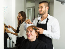 Mature woman cuts hair Royalty Free Stock Photography