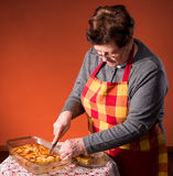 Mature woman cutting apple pie Royalty Free Stock Images