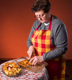 Mature woman cutting apple pie Royalty Free Stock Photography