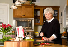 Mature woman cutting tomato. Stock Photography