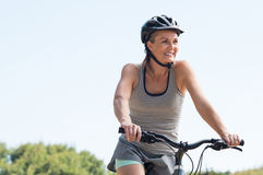 Mature woman cycling. Mature woman riding on mountain bike in the park. Portrait of a happy senior woman riding bicycle in a park. Athletic woman wih helmet stock photo