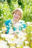 Mature woman daisy field Stock Photos
