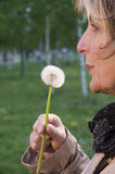 Mature woman with dandelion vertical Stock Photo