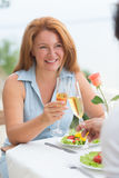 Mature woman dating. Dating concept. Red-haired woman smiling with a glass of wine in her hand. Happy woman enjoying summer evening with her man stock photos