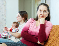 Mature woman and daughter with baby having conflict Stock Images
