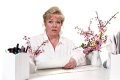 Mature woman at desk Stock Images