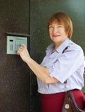 Mature woman dialing an intercom Stock Images