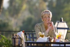 Mature woman dining at outdoor restaurant table, smiling, front view, portrait, wine in ice bucket beside table Stock Image