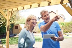 Mature Woman Discussing Plan With Landscape Gardener Using Digit Royalty Free Stock Image