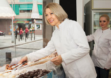 Mature woman display with pastry. Portrait of mature women at confectionery display with pastry royalty free stock photography