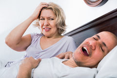 Mature woman disturbed with partner snores Stock Images