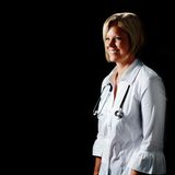 Mature Woman Doctor. Against black with stethoscope royalty free stock image