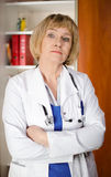 Mature woman doctor in white coat. Standind in front of shelf with medical files Stock Image