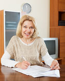 Mature woman with  documents at table Stock Photo