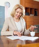 Mature woman with  documents and tea Stock Photos