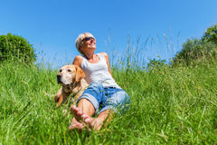 Mature woman with dog at a hiking rest Stock Photos