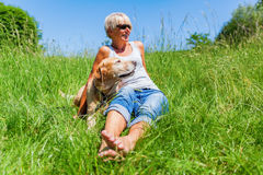 Mature woman with dog at a hiking rest Stock Images