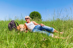 Mature woman with dog at a hiking rest Stock Photo