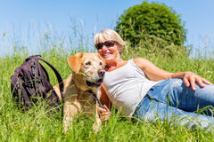 Mature woman with dog at a hiking rest Royalty Free Stock Photography