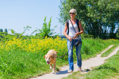 Mature woman with dog taking hiking in the country Stock Photo