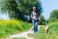 Mature woman with dog taking hiking in the country Stock Images