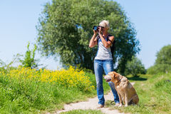 Mature woman with dog taking photos with a camera Stock Image
