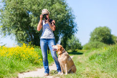 Mature woman with dog taking photos with a camera Royalty Free Stock Photo