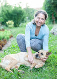 Mature woman with   dog in   yard. Stock Photo