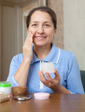 Mature woman doing cosmetic mask Royalty Free Stock Image