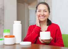 Mature woman doing cosmetic mask Stock Photography