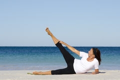Mature woman doing exercise at beach stock images