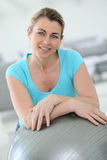 Mature woman doing fitness exercises. At home Stock Photo