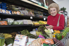 Mature Woman Doing Grocery Shopping. Portrait of smiling mature women with cellphone while doing grocery shopping in supermarket Royalty Free Stock Photography